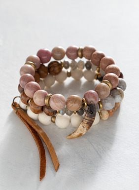 Set of 3 beaded stretch bracelets in a mix of round and faceted beads in soft hues of cream, grey, pink, purple and brown.  Combines brass spacers, wood beads, semiprecious stones, a leather tassel and a wolf tooth.