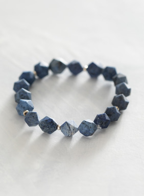 Star-cut dumortierite crystals are strung with brass spacers on the stretch bracelet.
