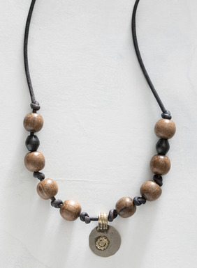 The handmade leather choker is strung with grey wooden beads and a vintage Indian pendant.