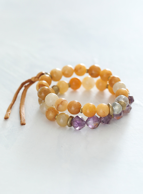 Reminiscent of desert hues, our stretch bracelets showcase smooth yellow jade, carcoxenite, and starcut brass beads.  Additional touches of green lodolite beading and cognac leather tassel details complete the set. Bracelets are strung to stretch over hand with ease for a secure fit on the wrist.