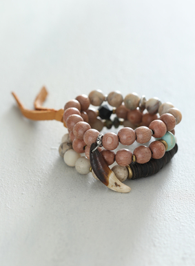 Romantics and nomads alike are sure to adore this boho-chic accessory. The set of 3 stretchy bracelets are a melting pot of semiprecious stones, coconut shells and metal findings, trimmed with a long suede tassel and wolf's tooth detail.
