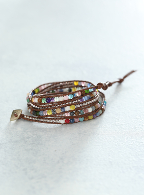 Leather cording and semiprecious stones make up this colorful wrap bracelet, complete with adjustable button and loop closure.  A stunning mix of quartz, crystal, and agate stones blend beautifully with pops of rosewood and brass beading.