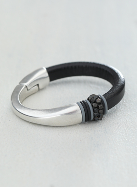 Chic and modern, our black leather and silver-plated metal bracelet features oxidized metal beading, alongside grey and black rings.  The bracelet also features a magnetic closure.