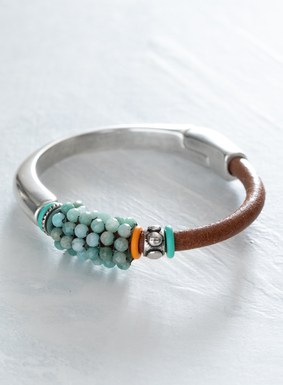 Our artful bracelet features amazonite and teal glass beads sewn alongside bright rubber rings and metal findings. The band is composed of sterling silver plate and Italian cognac leather, with faceted amazonite clasp.