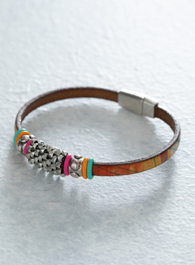 A chic way to add a touch of bohemian flair, our Painted Desert Bracelet is dusted with metal beadwork and colorful rubber rings. The leather band is printed with bright streaks of orange, teal, and emerald; metal magnetic closure.