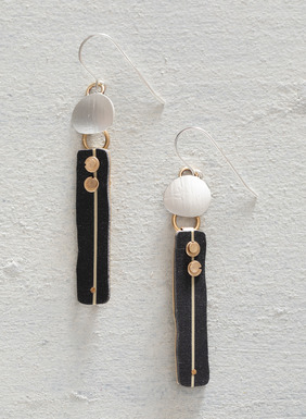 The sculptural earrings are handcrafted of sterling silver discs, polymer clay lozenges and brass rivets.