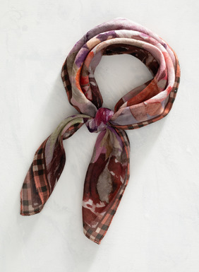 Large, watercolor primroses bloom in shades of pink, orange, brown, purple, and gold with soft green leaves with a petite plaid border in black, cream, and light brown. Made of cotton, this versatile square bandana can be worn around the neck, tied into hair, wrapped around the wrist, or worn in any other number of ways.