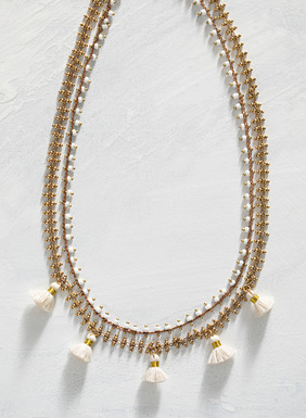 The handmade 14kt gold plate necklace is strung with tiny ceramic beads and ivory cotton tassels.
