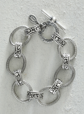 Our antiqued, sterling silver-plated bracelet is comprised of etched ovals and embossed links, with  a toggle closure. This piece pairs well with both sophisticated and casual ensembles.