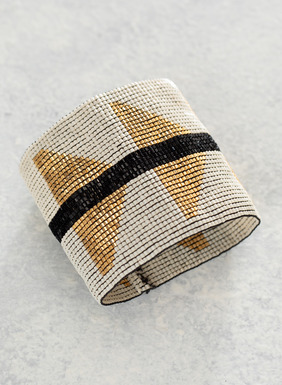 The handwoven, glass bead bracelet makes a bold statement in a graphic pattern of gold and white with a single black stripe.