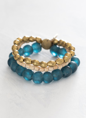The three-strand stretch bracelet is handcrafted with beads of glass, brass and coconut.