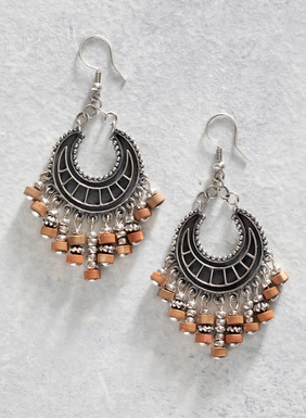Embracing a bohemian vibe, the sterling silver crescent moon earrings are artisan made and fringed with ceramic and silver beads.