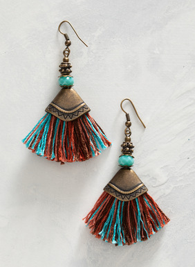 Antiqued bronze earrings are adorned with bright turquoise-hued glass and fan fringe.