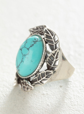 The handcrafted ring features a reconstituted turquoise stone wrapped in sterling silver leaves.