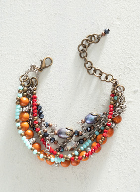 Made in Peru, this joyful multi-strand bracelet is composed of orange-colored wood beans, light blue, black, and red faceted crystals, and both silver-plated and copper-plated bronze chains with an easy-to-use, lobster claw closure. Sales support Peruvian cottage industries working to preserve traditional textile techniques.