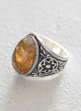 The artisan-crafted sterling silver ring is adorned in floral filigree and topped with an amber hued resin stone.