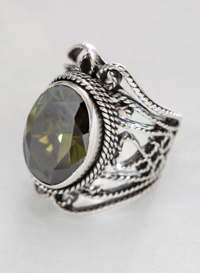 The handmade filigree sterling silver ring is topped with a faceted green crystal.