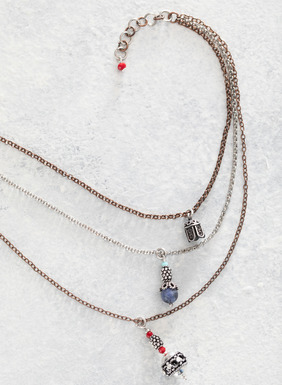 The artisan-made, three-strand necklace features bronze, copper and silver-plated chains that dangle petite silver and gemstone charms.