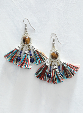 Add a touch of magic to your look with our Tiger's Eye Tassel Earrings. Thought to have protective powers, the tiger's eye stone is set in silver-plated bronze. Colorful cotton tassels swing below in shades of teal, rust, and cream, and feature brass and sodalite beading details.