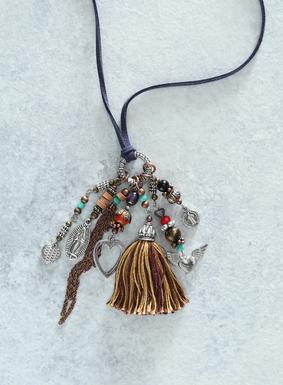 An der verstellbaren blauen Wildleder-Halskette prangt ein Potpourri aus versilberten peruanischen Milagro-Amuletten und Halbedelsteinen wie Jaspis, Tigerauge und Perle.  Eine farbenfrohe Quaste aus burgunderroten und messingfarbenen Garnen vollenden die charmante Halskette.