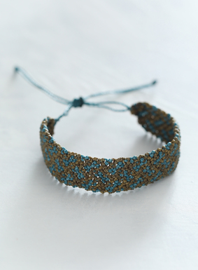 Add a touch of crochet to your accessory collection this spring with our Chicalyo Bracelet.  Artisan-made in Peru, the crochet cuff is bohemian mix of teal and brassy taupe waxed thread, complete with an adjustable slide closure.