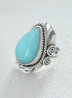 Make a statement with our sterling silver and amazonite cocktail ring.  Known for its soothing properties and balancing energy, the teardrop-shaped amazonite stone is set in an adjustable silver band featuring intricate scrollwork.