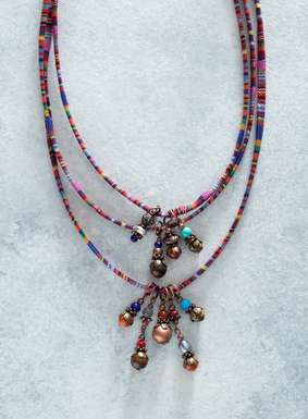 Crafted in Peru by hand, this colorful striped necklace is trimmed with tiger's eye, sodalite, jasper, reconstituted turquoise and bronze beads. Delicate leaves and spacers also hang from the multicolored manta striped fabric necklace.