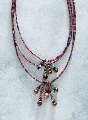 Unsere farbenfroh gestreifte Perlenkette wird in Peru von Hand mit Tigeraugen-, Sodalith-, Jaspis-, wiederaufgearbeiteten Türkis- und Bronzeperlen besetzt. An dem mit vielfarbigen Mantastreifen bedruckten Stoff hängen zudem zierliche Blätter und Distanzstücke.