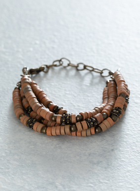 Sand and blush colored ceramic beads are strung on the artisan-crafted bracelet, with silver-plated bronze beads and spacers. The 5 strands feature an antique brass clasp and extender for versatility of placement and comfort.