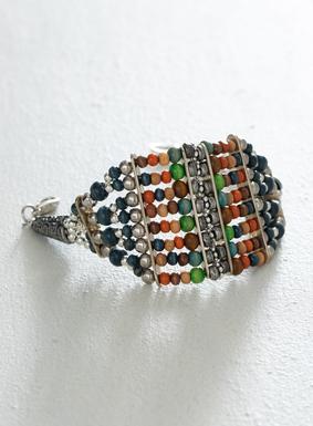 Von Kunsthandwerkerinnen in Peru hergestellt: Den Armreif zieren verschiedenfarbige Holzperlen und mit antikisierter Silberplattierung versehene Fundstückchen, die zwischen zwei geätzte kegelförmige Perlen gezogen sind. Der kunstvolle Armreif hat einen Spangenverschluss und verstellbare Ringe für Tragekomfort.