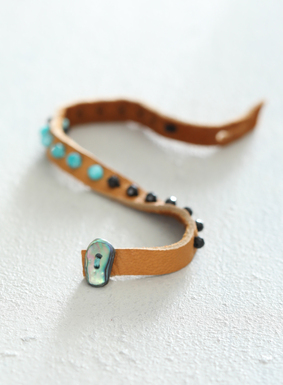 A boho-chic accessory for the wrist, our camel-colored deerskin leather bracelet is dotted with blue amazonite and black spinel beads. The bracelet also features an abalone shell closure detail. Known for its protective and healing qualities, the abalone shell is said to bring safety from harm and emotional balance.