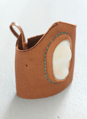 "Our statement cuff of whisky-hued deerskin is accented with a natural sea shell, and is outlined with contrast turquoise stitching.  The 3"" wide leather cuff makes for an impressive focal point in any ensemble."