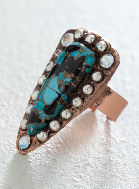 Silver-plated brass baubles and Swarovski crystals outline a teardrop blue Mojave turquoise stone.  Crafted by hand, the statement stone is set atop an antiqued copper band; adjustable.