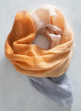 The gauzy linen scarf is dip dyed in orange, cream and ice blue.