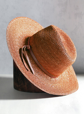 Once a symbol of the women's rights movements, the classic fedora hat features a traditional indented crown.  Made of straw, our fedora is trimmed with a leather band. Try styling it with your favorite spring maxi-dress, jumpsuit, or knit sweater.