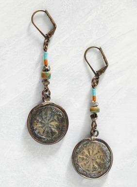 An den Ohrringen baumeln patinierte, mit antikisierten Dharma-Rädern verzierte Messingscheiben von bunten Perlenkettchen herab.