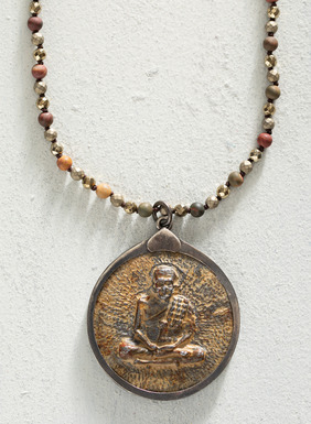 The faceted bead and stone necklace culminates with a cast brass Buddha medallion.