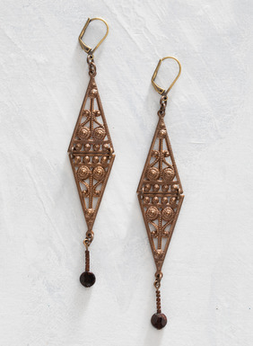 The Art Deco-inspired, hinged brass filigree earrings are tipped with faceted garnet rondelles.