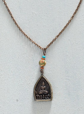 A seated brass Buddha hangs from a brass chain strung with beads of Tibetan agate, orange-colored bone, and turquoise beads. The pendant necklace is an artful way to add a little zen to your wardrobe.