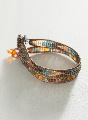 Set of 2 bracelets weaves sparkle in faceted glass beads strung on strands of coppery leather.