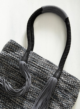 The cool, beachy tote is woven of space-dyed pima yarns in faded denim hues, with suede-wrapped handles and tassels.