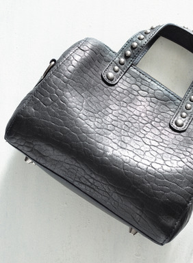 "Chic and edgy, this crocodile-embossed black leather handbag is sized for night-out essentials. It features two silver-studded handles and an adjustable, removable leather strap so the purse can also be worn across the body or draped on the shoulder. This purse is fully lined with one interior pocket a zip-top closure. The <a href=""https://www.peruvianconnection.com/product/256452-diamante+pima+bag+strap.do"" target=""_blank"">Diamante Pima Bag Strap</a>, pictured in the catalog, sold separately."