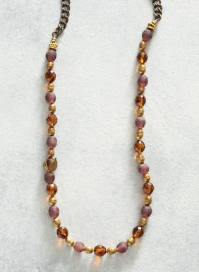 The handmade and layerable necklace is a mix faceted amber hued and frosted purple glass beads.