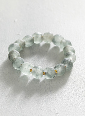 Handmade frosted seagreen hued glass stretch bracelet with petite brass spacers.