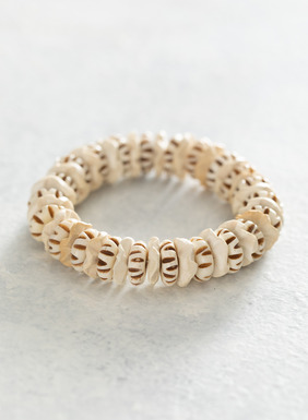 The stretchy bracelet is a beachy mix of wood and hand-carved bone.