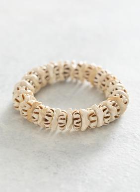 Unser elastisches Armband ziert ein sommerlicher Mix aus Holz und handgeschnitzten Knochen.