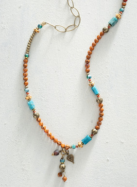 Cast in a Southwestern palette, this enchanting necklace features an asymmetrical brass chain strung with apatite, bone, glass beads, and a cluster of tiny charms. Made in the USA.