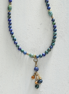Cast in deep ocean blues, the enchanting necklace features a sliding cluster of colorful Czech glass, chrysocolla, and brass beads. Beautiful on its own, this necklace can also be easily layered with other accents for a bolder statement.