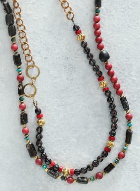 Die aufsehenerregende Halskette in kräftigen Farbtönen zieren Glas-, Granat-, Türkis- und Jadeperlen sowie Messingstückchen.