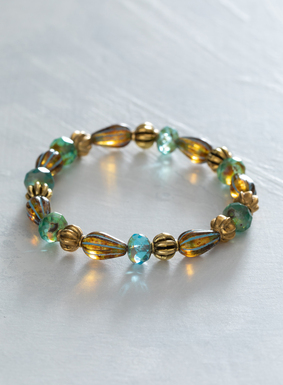 Textural turquoise and amber-colored Czech glass beads adorn the stretch bracelet, with brass bead accents. Easily worn with other bracelets or striking on its own, the bracelet pairs beautifully with many of the season's colorful prints.